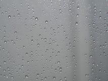 Regn tappar på fönsterexponeringsglas, modell av regndroppar som isoleras på exponeringsglasyttersida arkivbild