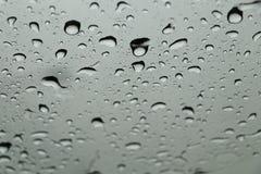 Regn tappar på främre fönster för bil i regnig dag royaltyfri fotografi