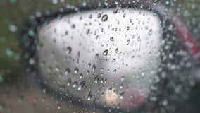 Regn tappar på spegeln för den bakre sikten och sidofönstret lager videofilmer
