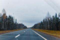 Regn tappar på vindrutan och den suddiga höstskogvägen på bakgrund Royaltyfria Foton