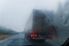 Regn tappar på vindrutan och den suddiga lastbilen i skogväg Omkörning av lastbilen låg synlighet Arkivbild