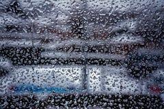 Regn tappar på yttersida för fönsterexponeringsglas med molnig bakgrund arkivfoto