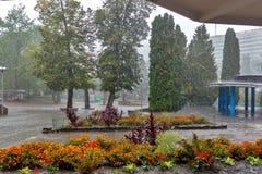 Regna i staden, regndroppanderna in i en pöl arkivbild