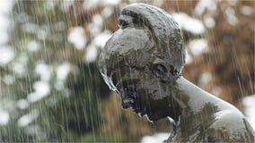 Regna nedgångar över huvudet av den kvinnliga statyn stock video