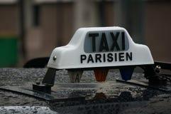 Regna på en svart Paris taxi med ett vitt taxiParisien tecken överst Arkivbild