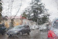 Regna på stadsgatan till och med en bilvindruta Regndroppar på fönstret, regnigt väder royaltyfria foton