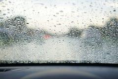Regna små droppar på bilvindrutan, blockerad trafik arkivfoton