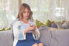 Regnancy、母性、技术、人们和期望概念-有智能手机的愉快的孕妇在咖啡馆的沙发 免版税库存图片