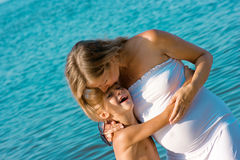 Рregnant mother kissing her son. Mother kissing her son's forehead Stock Image