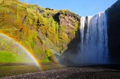 Regnbågar som går till och med vattenfallet Skogafoss Arkivbild
