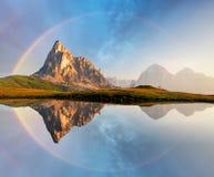 Regnbåge över berg sjöreflexion, Dolomites, Passo Giau Arkivbilder