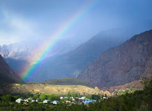 Regnbåge över byn i bergen Landskap tonat Arkivfoton