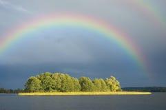 Regnbåge över en ö Fotografering för Bildbyråer