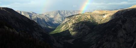 Regnbåge över en avlägsen bergskedja Arkivfoton