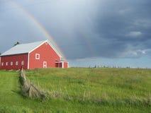 Regnbåge över en röd ladugård den bästa saker i liv är fri Arkivbild