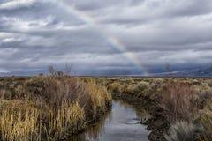 Regnbåge över ett träsk och kanal på en stormig dag Royaltyfri Foto