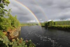 Regnbåge över floden Arkivbild