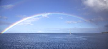 Regnbåge över havet arkivbild