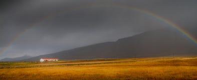 Regnbåge över lantgård i Island Royaltyfri Bild