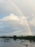 Regnbåge över sjön med moln Arkivbild