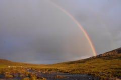 Regnbåge över tältläger på berget Arkivfoto