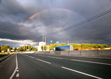 Regnbåge över vägen i staden Royaltyfria Bilder