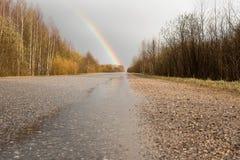 Regnbåge efter regn över vägen och den gamla byn Royaltyfria Bilder