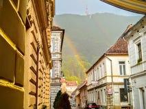 Regnbåge i den gamla mitten av Brașov Regnig dag och gammal husarchitecturure arkivfoto