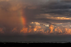 Regnbåge i en storm på solnedgången Arkivbilder
