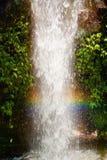 Regnbåge i en vattenfall Arkivfoto