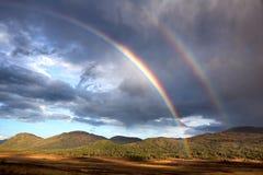 Regnbåge i höstbergen Arkivfoto