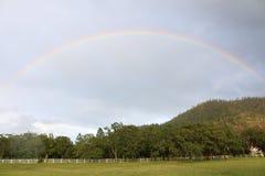 Regnbåge i landet efter vår Rainshower arkivbild