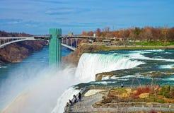Regnbåge i Niagara Falls och regnbågebro över Niagara River Fotografering för Bildbyråer