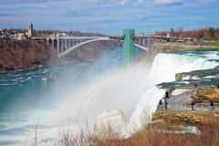 Regnbåge i Niagara Falls och regnbågebro ovanför Niagara River Arkivfoto