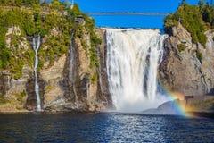 Regnbåge i sprejen av en vattenfall Arkivfoto