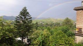 Regnbåge med härligt landskap arkivfoto