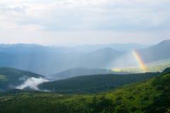 Regnbåge och dimma i bergen över husen Arkivfoton