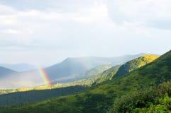 Regnbåge och solljus i bergen över husen Arkivfoton