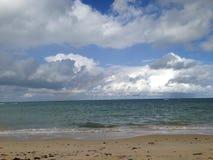 Regnbåge och strand arkivfoton