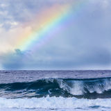 Regnbåge och våg Arkivbilder