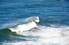 Regnbåge på en våg Arkivbild