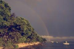 Regnbåge som bildar över havet efter åskastorm arkivfoton