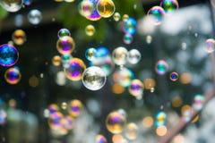 Regnbågebubblor slänger i luften ut ur fokusbakgrund royaltyfri bild
