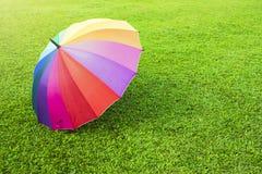 Regnbågefärgparaply på grönt gräs arkivbild