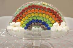 Regnbågefödelsedagkaka på kakaställning Arkivfoto