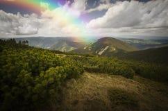 Regnbågen över landskap och vit fördunklar på blå himmel Arkivbild