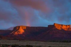 Regnbågen över rött vaggar Mesa i Utah under storm och solnedgång Royaltyfria Foton