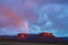 Regnbågen över rött vaggar Mesa i Utah under storm och solnedgång Royaltyfri Foto