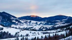 Regnbågesikt av kalla berg för vinter på gryningträstaketet i sn Arkivfoton