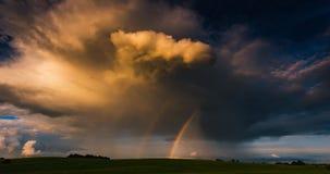 Regnb?gen gl?der i solljuset mot bakgrunden av m?rka moln Skuggor av solen fortskrider 4K TimeLapse lager videofilmer